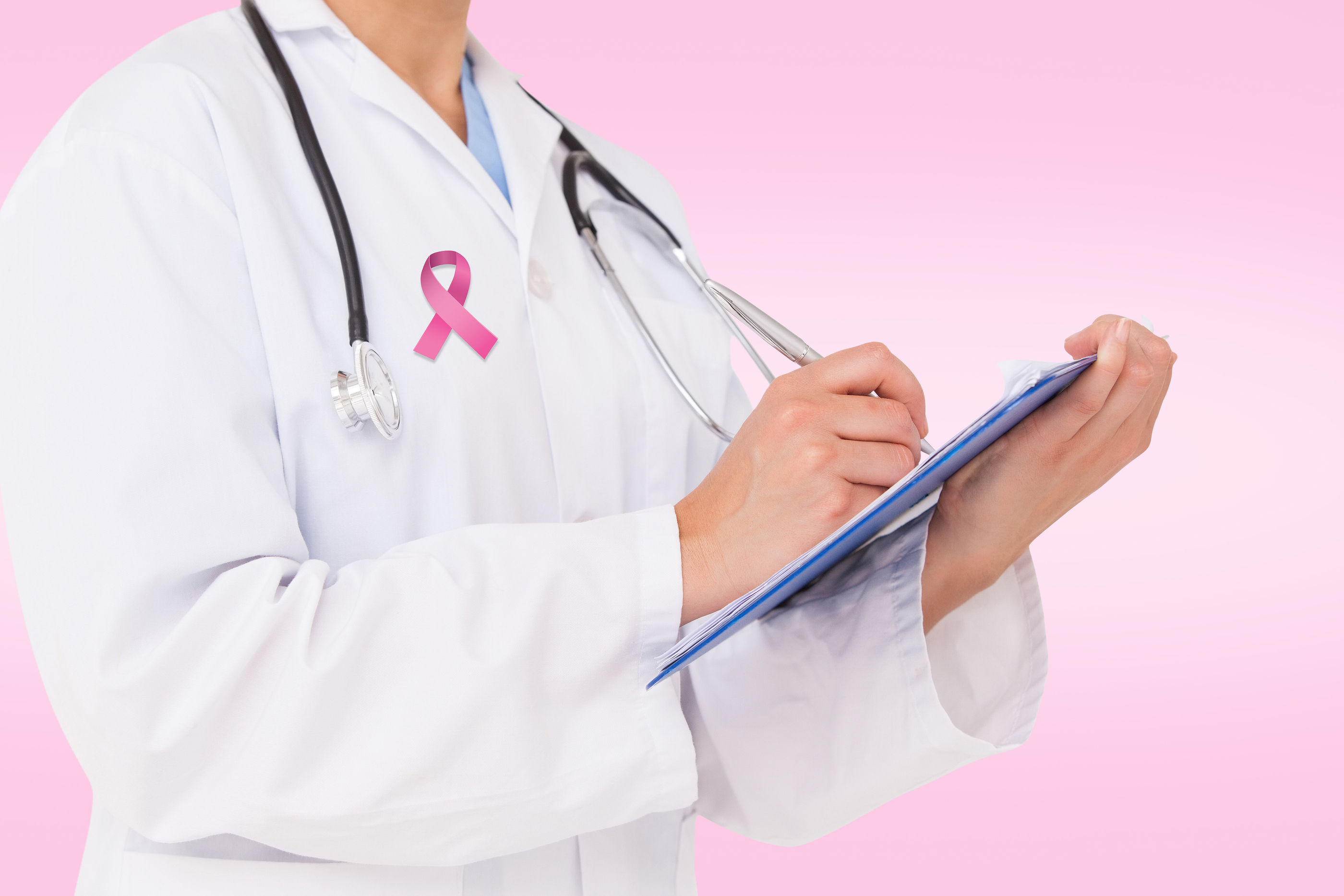 Doctor writing on clipboard against pink