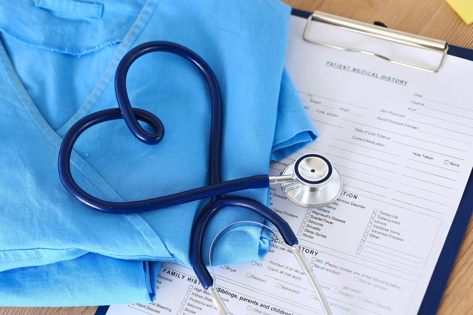 Medical stethoscope twisted in heart shape lying on patient medical history list and blue doctor uniform closeup. Medical help or insurance concept. Cardiology care health protection and prevention