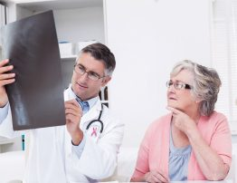 Pink awareness ribbon against doctor explaining x-ray to female patient