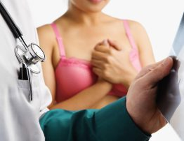 Doctor examine xray slide with nervous woman in pink bra waiting on background