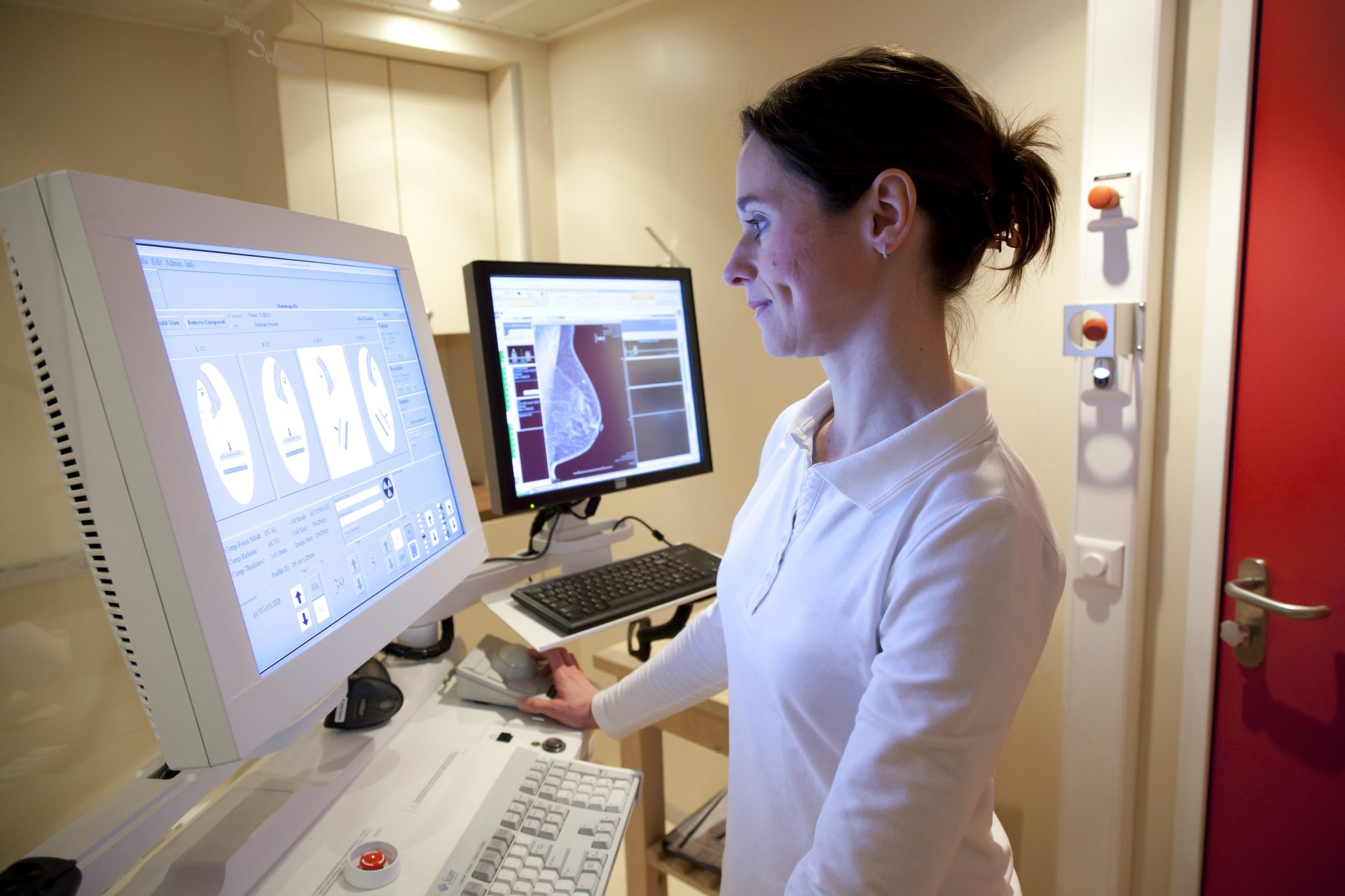 Female radiology technician performs mammography test on computer
